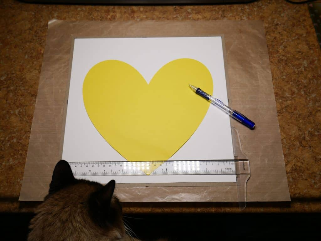 Tracing a heart onto your card stock paper to create a shadow box using your Cricut.