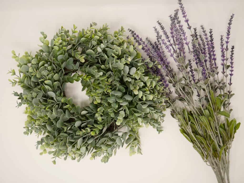 A wreath made with all green stems of a Eucalyptus tree with 13 pieces of the Lavender flower stalks tucked into and around the greenery.