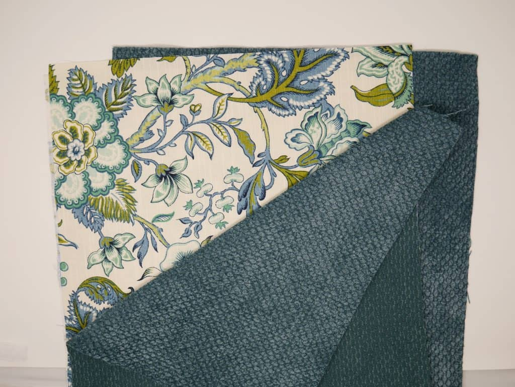 1 piece of Blue textured piece of home decor fabric and 1 piece of blue and green leaves and flowers home decor fabric.