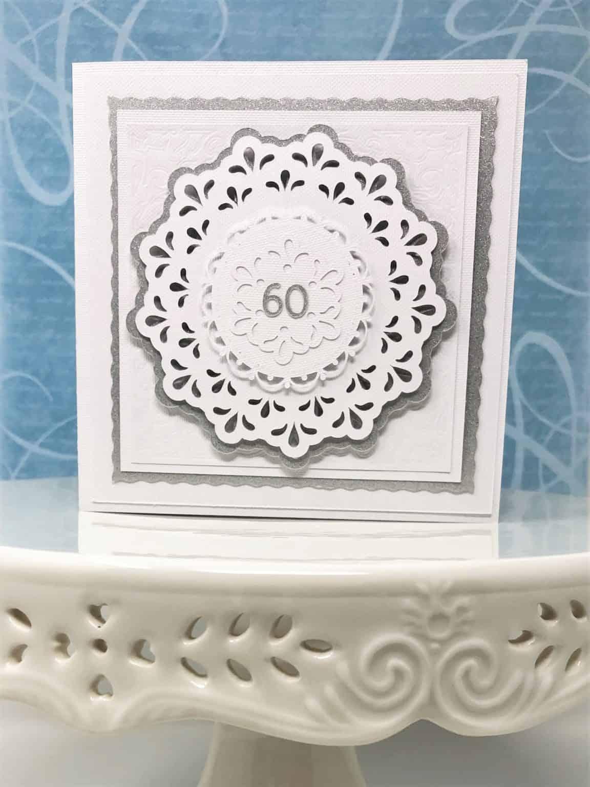 beautiful Cricut anniversary card sitting on a ceramic pedestal