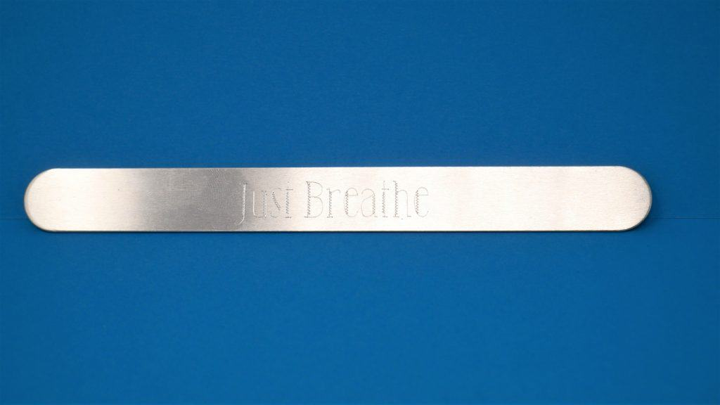 "close up picture of the engraving ""just breathe"" on the aluminum bracelet"