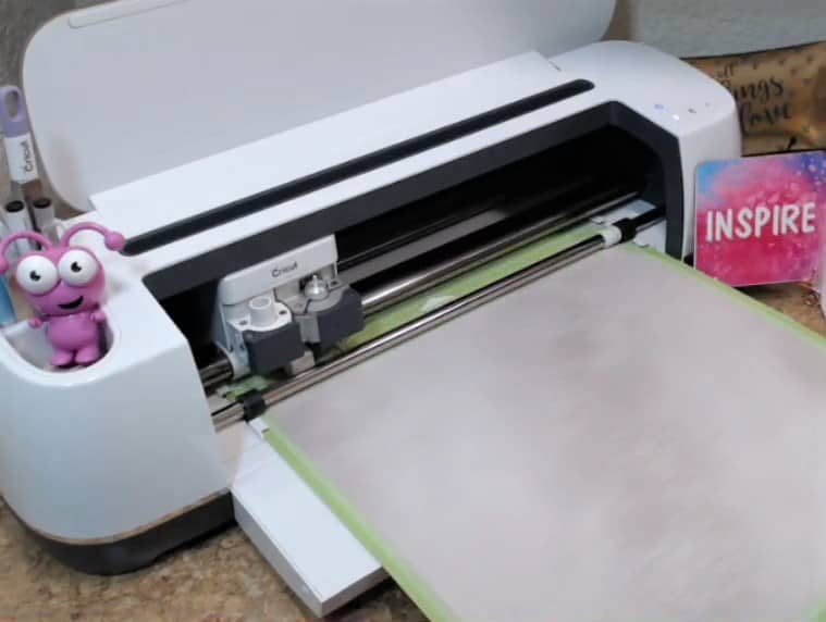 Loading your cricut mat into the cricut cutting machine so it will cut out your Man Cave design from the infusible ink transfer sheet.
