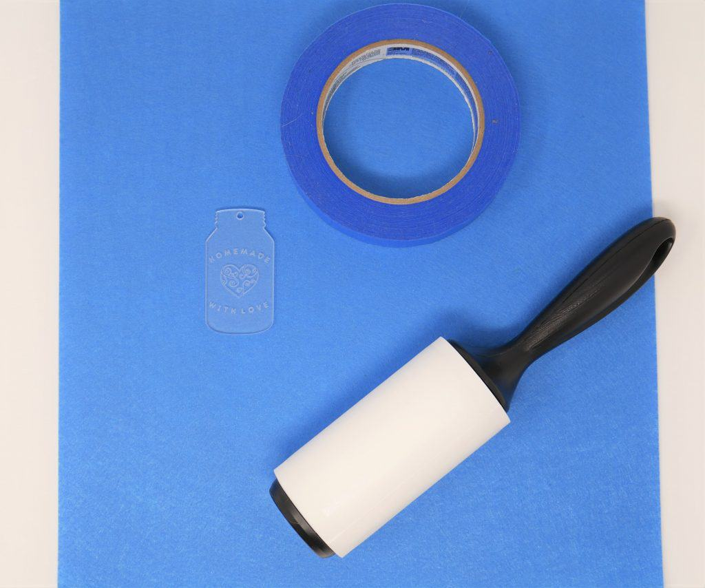 engraved label, blue tape and a lint roller