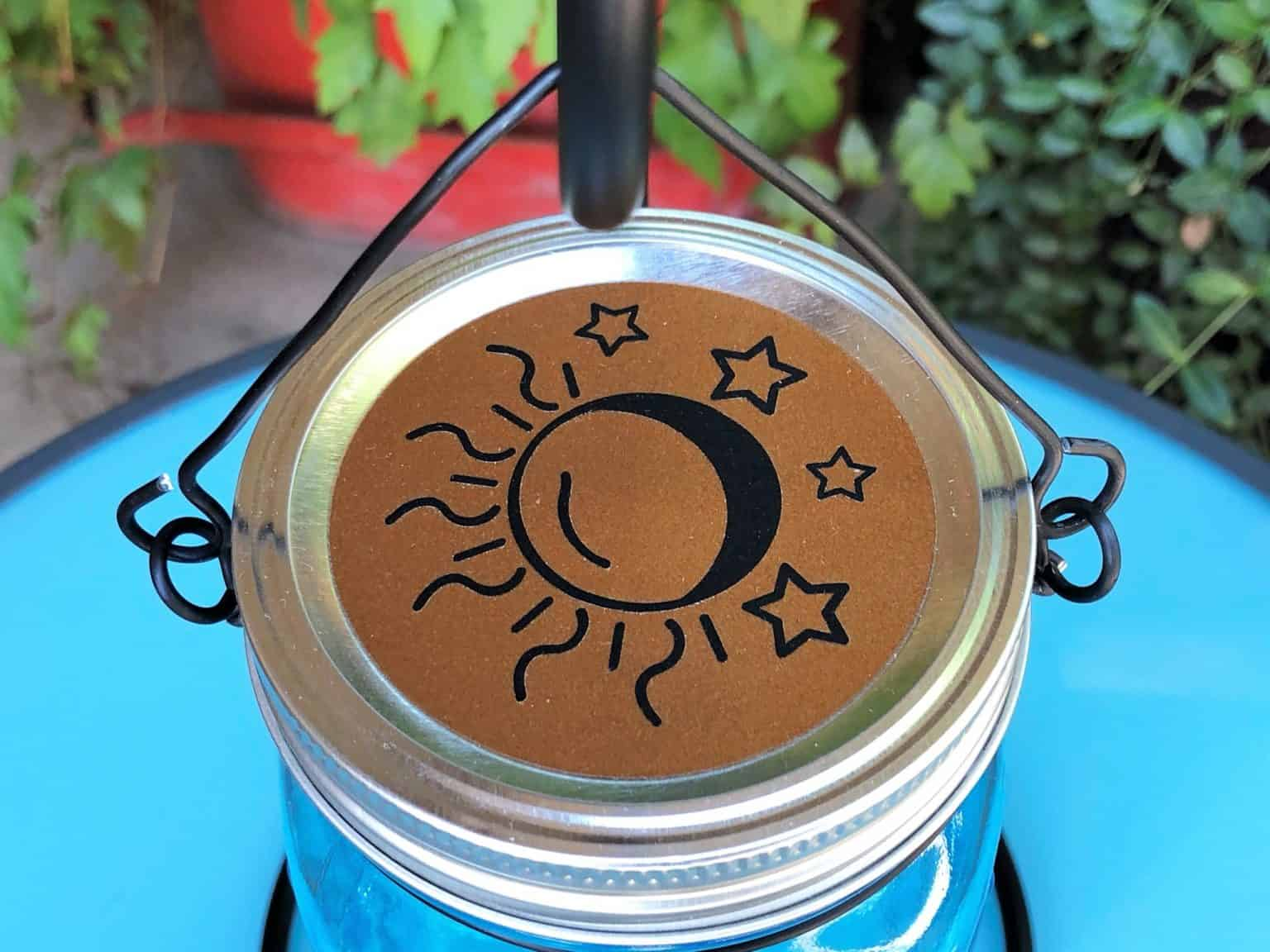 close up picture of wire hanger with sun and moon file in vinyl on the lid