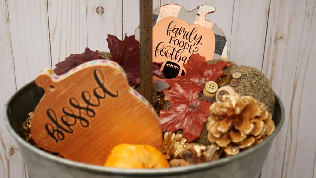top tier of fall tiered tray holding painted wooden shapes with htv on them
