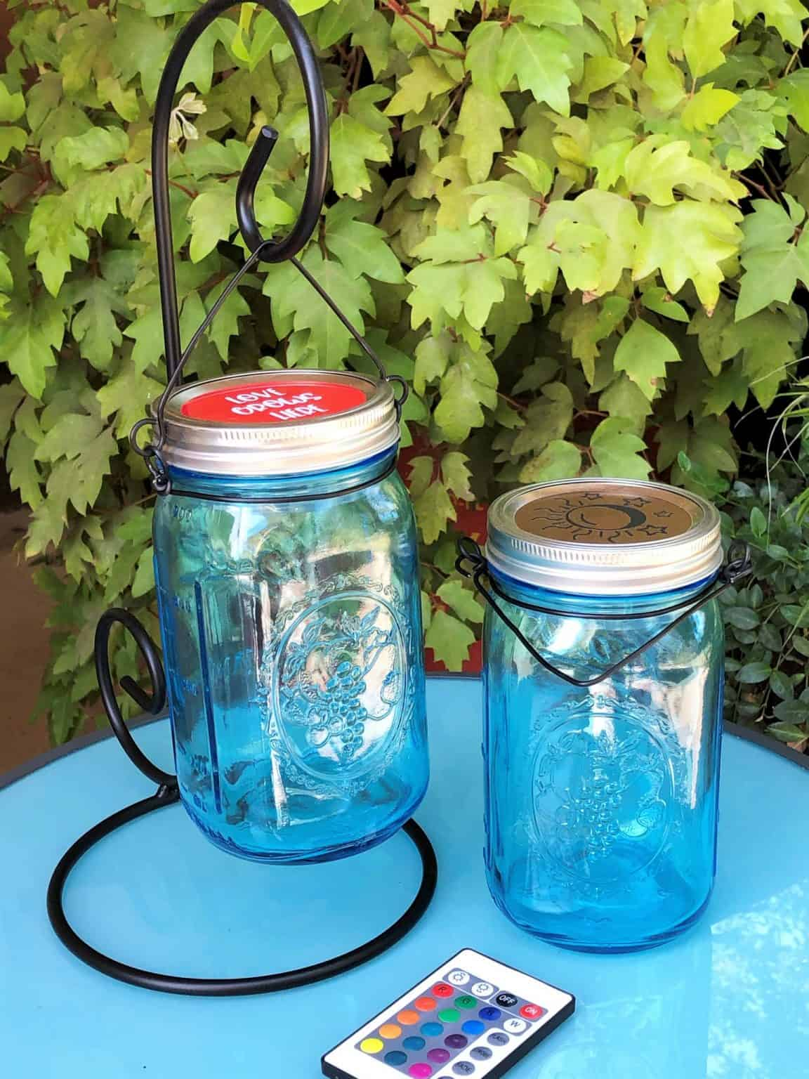 2 blue mason jar canning jar lights one hanging from a stand and the other one is setting on top of a patio table.