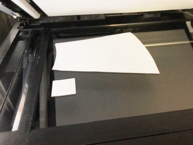 a printer/scanner showing a paper pattern piece and a 1 inch test square laying face down on the scanner bed to scan to upload into a computer